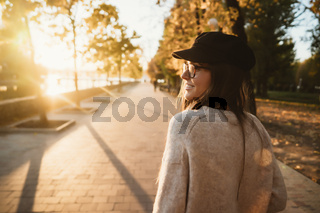 Attractive, young brunette with long hair walking autumn park.