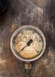 an old round pressure meter with numbers on the gauge on a rusty metal background