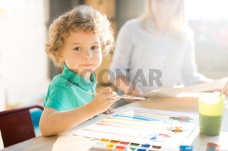 Curly Haired Boy Painting in Sunlight