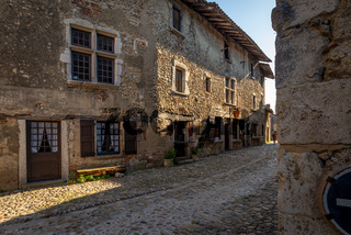 Tourist entering a cobblestone street of Perouges, France