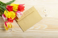 Colorful tulips and blank envelope on natural wooden background with space for text