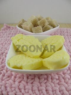 Frische selbstgemachte Butterstückchen und gewürfelte Brotstückchen