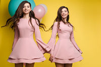 Cute brunette twins in pink dresses over yellow background.
