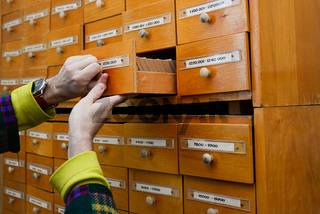 A person's hand opens a library card or file directory. Database concept. Antique cabinet in library with boxes for storing information