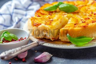 Piece of tarte tatin pie with potatoes close-up.