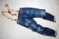 Jeans Hose mit Hosenträgern auf einem Betonboden