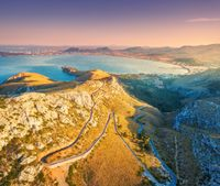 Aerial view of mountains, road, trees, blue sea at sunset