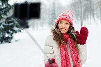 young woman taking selfie by monopod in winter