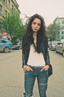 Modern girl standing outside in rip-jeans in the center of the street