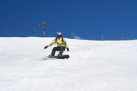 Snowboarder descends on snowy ski slope at winter mountain