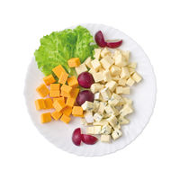 Cheese plate served with grapes and lettuce. Top view