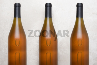 Chardonnay Wine: Top view of a three bottles on a concrete counter top.