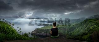 Panorama einer Küstenlandschaft mit einer Frau im Vordergrund