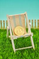 Bitcoin Münze in Liegestuhl als Altersvorsorge Konzept