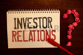 Handwriting text Investor Relations. Concept meaning Finance Investment Relationship Negotiate Shareholder Reddish paper balls structures question mark red pen notebook browny desk.