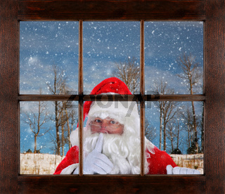 Santa Claus peeking in window making Shh sign, finger to mouth, with snowy winter scene in the background.