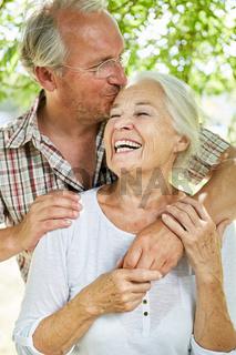 Senior Mann küsst seine lachende Ehefrau