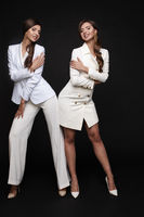 Stylish women in white smart suit and dress posing