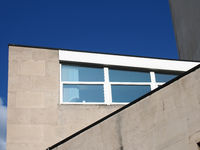angular close up view of an old 1960s concrete brutalist stye building with blue sky