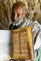 Orthodoxer Priester der Felsenkirche Mikael Mellehayzengi zeigt handgeschriebenes Buch, Äthiopien