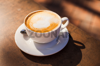 The cup of coffee on the table outdoor