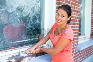 Colombian woman with paint scraper at window frame