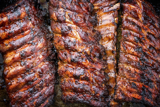 Barbecue spare ribs St Louis cut with hot honey chili marinade as top view copy space and food texture