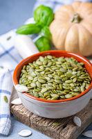 Raw pumpkin seeds in a ceramic bowl.