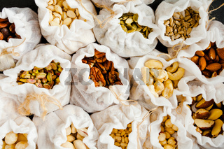 Eco pouches with various types of nuts on black background. Zero waste shopping concept