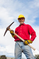 Contractor, builder using a pick with Yellow Hardhat outdoors