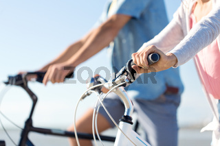close up of young couple riding bicycles on beach