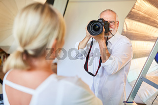 Fotograf mit digitaler Kamera macht Porträtfotos