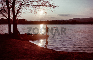 Man fishing at the water at sunset or sunrise. Shot on analog film.