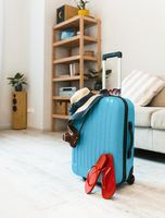 Blue plastic suitcase with hat, havaianas in the room.