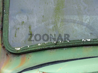 close up of the windscreen of an old abandoned pick up truck with the steering wheel visible through stained moss covered glass