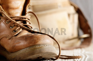 Yellow leather used work boots and tool belt on wooden background closeup. Place for text