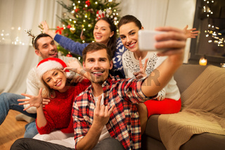 friends celebrating christmas and taking selfie