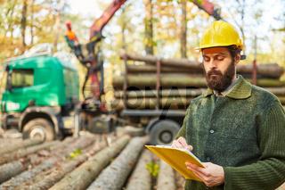 Forstwirt mit Checkliste beim Verladen von Langholz