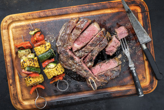 Barbecue dry aged wagyu cutlet with vegetable skewer as top view on a burnt cutting board