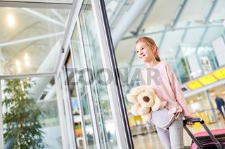 Alleinreisendes Kind mit Gepäck im Flughafen