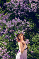 beautiful girl in purple dress with lilac flowers