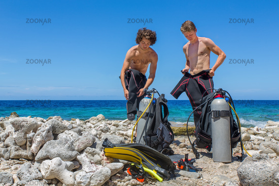Two divers change clothes at the beach