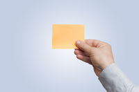Mle hand in light blue shirt hold an orange blank sticky note on gradient white to light blue background