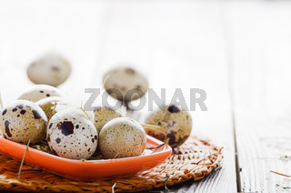 Fresh organic quail eggs in orange clay plate on wooden rustic kitchen table. Space for text