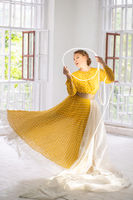 Dancer In A Yellow Dress Makes Pa Holding A Glowing Circle In Her Hands.