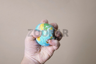 hand crushing globe of planet earth - ecocide or destruction of environment concept