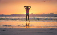 Young woman standing in sea with waves at sunset