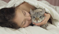 Happy teen girl kisses and talks with Thai cat in bed
