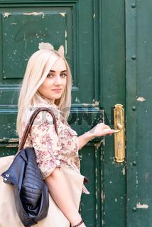 Junge blonde Frau bei Haustüre