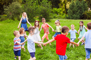 Happy kids dancing in circle on green lawn in park